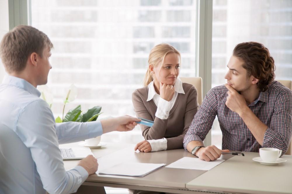 Ein Bankangestellter versucht mit einem nachdenklich dreinschauenden Pärchen über einen Kredit zu sprechen.